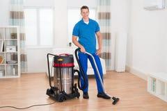 Portero de sexo masculino Vacuuming Floor Fotos de archivo libres de regalías