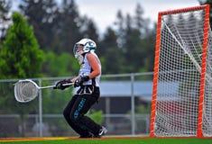 Portero del lacrosse del equipo universitario de las muchachas que toma un golpe Fotografía de archivo libre de regalías