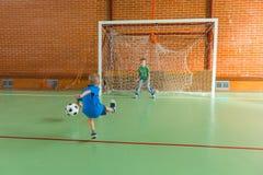 Portero que golpea el balón de fútbol con el pie Foto de archivo