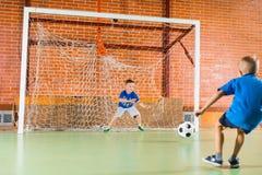 Portero que golpea el balón de fútbol con el pie Fotografía de archivo libre de regalías