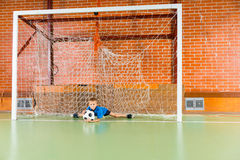 Portero que golpea el balón de fútbol con el pie Imagenes de archivo