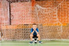 Portero que golpea el balón de fútbol con el pie Imágenes de archivo libres de regalías