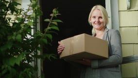 Portero una mujer con un paquete en sus manos Está en el umbral de la casa, mirando la cámara Familia de bajos ingresos metrajes