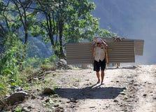 Porteros de Nepal que llevan la carga pesada en el suyo detrás. Fotografía de archivo
