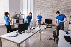 Porteros que limpian la oficina foto de archivo