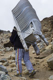 Porters carry heavy load in the Himalaya Stock Photography