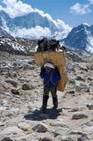 Porters carry heavy load in the Himalaya Stock Images