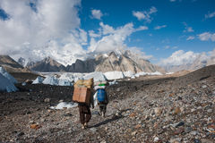 Porters carrying heavy loads in Karakoram. Trekking in Karakoram mountain range, Northern Pakistan Stock Image