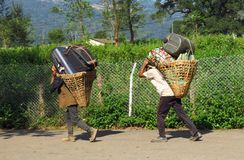 Porters carrying heavy luggage in a basket fixed with a head strap, Tumlingtar, Khandbari, Nepal. Hard working sherpas carrying heavy luggage and suitcases in a royalty free stock photos
