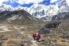 Porters with heavy load after crossing Cho La Pass in Himalayas. Royalty Free Stock Images
