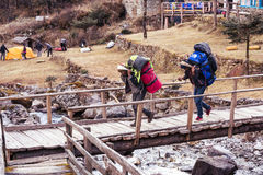 Porters of Himalaya Mountain expedition crossing wooden bridge. Porters of Himalaya Mountain expedition carrying heavy bags walking crossing wooden bridge Royalty Free Stock Photo