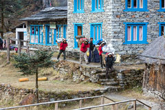 Porters of Himalaya Mountain expedition walking throw village. Porters of Himalaya Mountain expedition carrying heavy baskets and bags walking throw village Stock Images