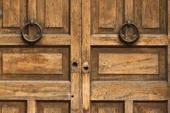 Portes à deux battants en bois avec les heurtoirs en laiton ronds photos libres de droits