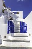 Portes bleues avec de beaux petits groupes d'escaliers blancs d'île de Santorini, photos libres de droits