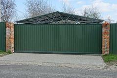 Portes de long vert faites en métal et partie d'une barrière près d'une route goudronnée photos stock