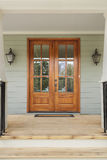 Portes en bois jumelles à une maison familiale verte Image libre de droits