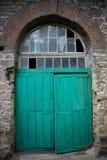 Portes en bois vertes dans un mur en pierre Image stock