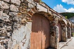 Portes en pierre arquées avec des portes de chariot le long de rue urbaine dessus Photos stock