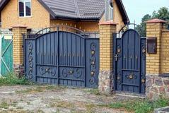 Portes et portes noires en métal avec un modèle et une pièce forgés d'une barrière de brique Image stock