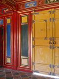 Portes jaunes lumineuses contre un mur rouge, bleu et vert coloré avec les détails d'or images stock