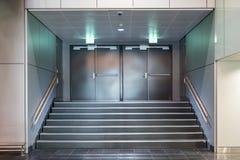 Portes métalliques de sortie de secours avec l'escalier photographie stock