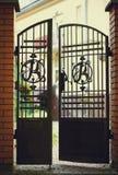 Portes noires de fer travaillé et d'entrée de brique Photo stock