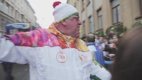 Porteur de flambeau d'étreinte de volontaires Course de relais de flamme olympique de Sotchi dans le St Petersbourg assistances banque de vidéos