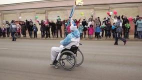 Porteur de flambeau dans un fauteuil roulant portant une torche sur le relais de torche de Paralympic banque de vidéos