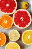 Portez des fruits dans un plan rapproché de coupe, pamplemousse, orange, citron, mandarine, fond de fruit Nourriture rustique fru Photo libre de droits