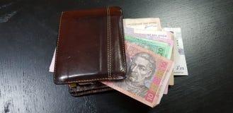 Portfel folował z hryvnia banknotami kłaść na czerń stole obrazy stock