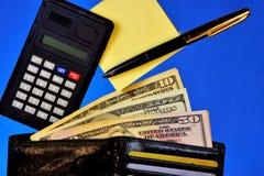 Portfel z pieniądze różny banknotu kalkulator dla zapłat i bank karty, majcher, pióro na błękitnym tle ogłoszenie towarzyskie obraz stock