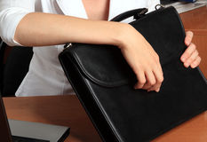 Portfolio in female hands. The woman at office holds in hands a black portfolio Stock Image