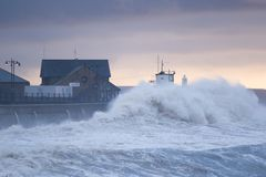 Huge waves crash over the seafront at Porthcawl, South Wales stock images