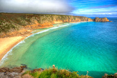 Porthcurno beach Cornwall England UK near the Minack Theatre IN hdr. Turquoise sea at Porthcurno beach Cornwall England UK near the Minack Theatre in vivid Stock Photography