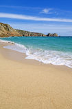 Porthcurno sandy beach and Logan rock in Cornwall England. Royalty Free Stock Images