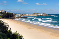 Porthminster beach and St Ives Cornwall England with white waves and blue sea and sky. Porthminster beach with St Ives Cornwall harbour in the background in stock photo