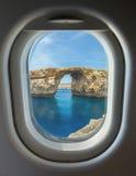 Porthole, Azure Window, stone arch of Gozo, Malta. Porthole and landmark, Azure Window, famous stone arch of Gozo island through the window of the plane against Royalty Free Stock Photo