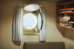 Porthole in the cabin of an old yacht Stock Images