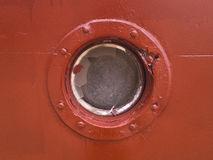 Porthole on the red wall of the old ship stock photos