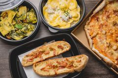 Porti via l'alimento italiano della pasta Pizza con i peperoni verdi, il pane all'aglio, il fetuccine ed i ravioli della scatola  fotografia stock