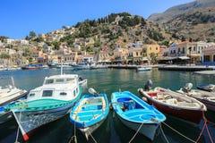 Porticciolo alla cittadina Symi con le barche e le case variopinte Immagine Stock Libera da Diritti