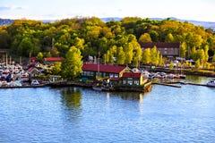 Porticciolo con le barche e le costruzioni nel porto, Norvegia Fotografie Stock Libere da Diritti