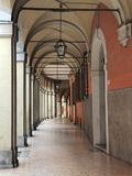 A portico in Bologna, Italy. A lamp hanging from the arched roof. stock photos