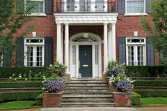 Portico entrance. A large house, nicely landscaped, with a portico style entrance royalty free stock images