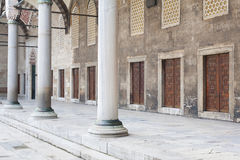 Portico with marble columns and doors in a row in the courtyard. Of an ancient mosque Royalty Free Stock Images
