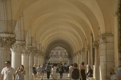 Portico of St. Mark square. Arcades of Piazza San Marco in Venice with the underlying passage full of tourists visiting the city Stock Image