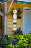 Portiek en ingang aan lokaal geel houten Key West-huis met bouys en installaties die door deur hangen stock foto