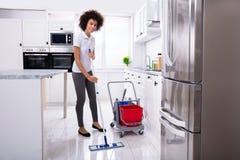 Portier Cleaning The Floor met Zwabber stock afbeeldingen