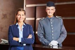 Portier en receptionnist in hotel als team stock fotografie