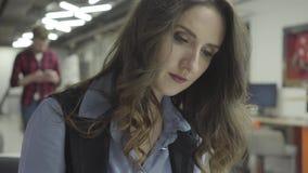 Portier van een succesvol bedrijfsmeisje met donker documentair zittingshaar in een bureau De Businesslodywerken in stock videobeelden